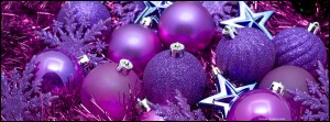 Background arrangement of purple Christmas decorations with tinsel, stars, baubles and snowflakes